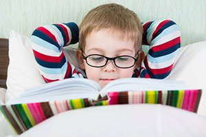 Image of a child reading in bed wearing glasses.