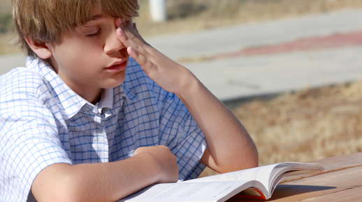 teen rubs left eye while reading