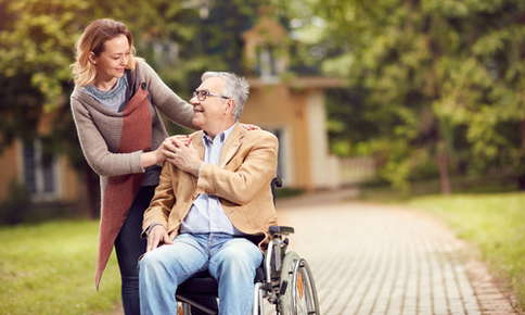 Woman caregiving for man in a wheelchair