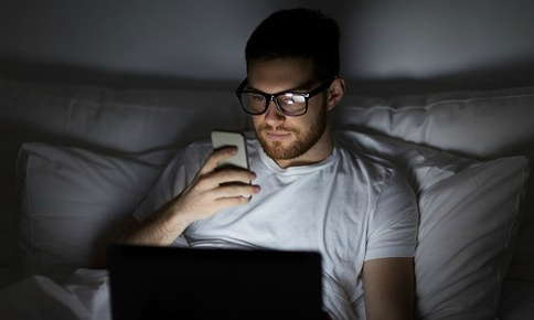 Man on phone and laptop in bedroom