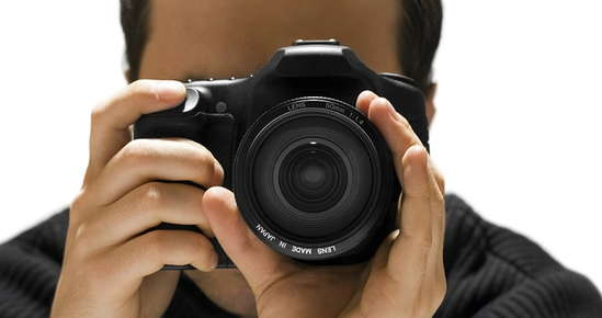 Image of a man focusing a digital camera.
