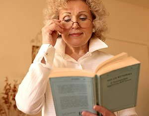 Image of an elderly woman wearing glasses and reading a book.