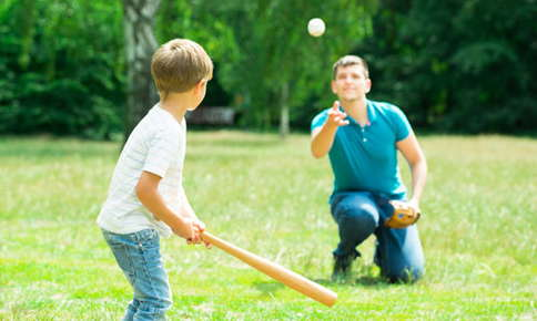 boy playing baseball with father