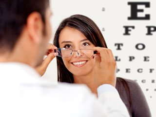 Image of an optometrist helping a patient try on a pair of glasses.