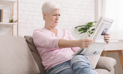 Woman squinting while reading the newspaper