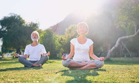 Image of two seniors seated in a yoga position outside in the park.