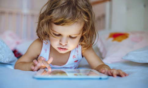 Image of a young girl who is playing on a digital tablet.