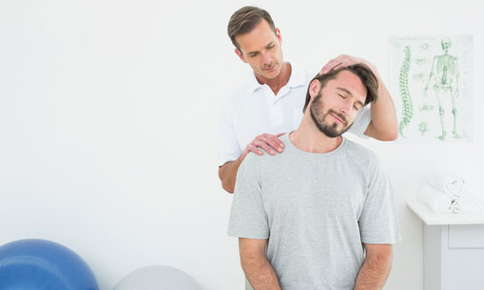 A picture of a chiropractor giving a patient an adjustment by tilting the patient's head and apply pressure to his shoulder.