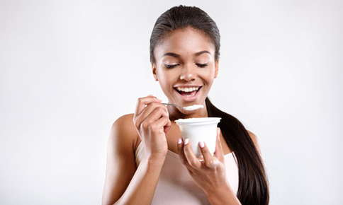 A picture of a woman eating yogurt that contains probiotics.