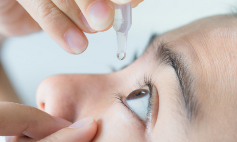 Woman using eye drops