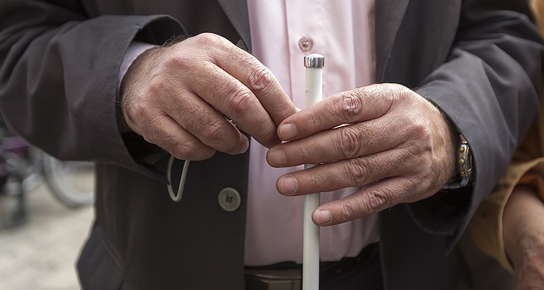 two hands holding white cane
