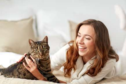 image of woman holding cat on a bed.