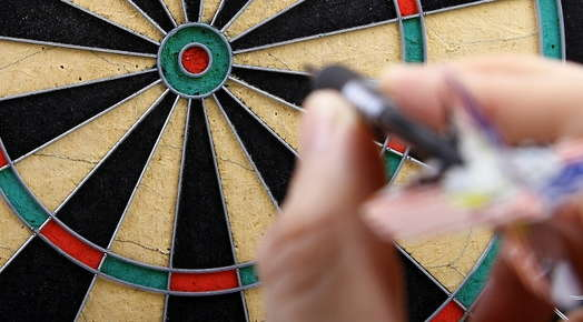 hand aiming to throw dart