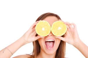 Image of a woman holding lemons to her eyes and smiling.