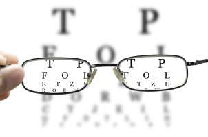 hand holding glasses to eye chart