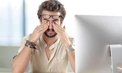 Man rubbing eyes after looking at computer screen