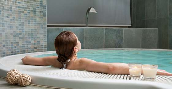 Image of a woman relaxing in a large bathtub.