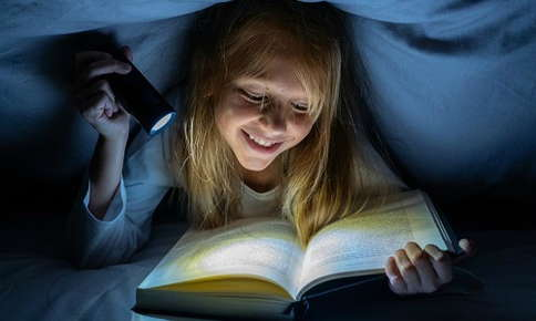 Young girl reads in the dark