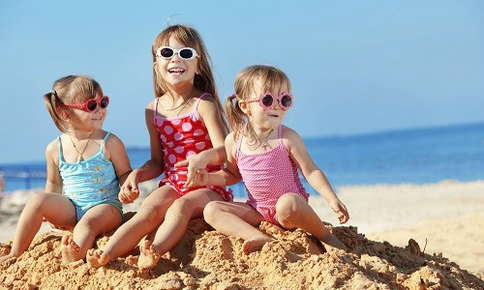 Kids protecting their eyes in sunglasses at the beach