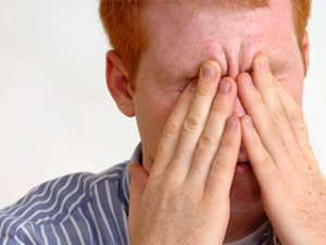 Image of a man rubbing his eyes.
