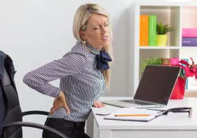 image of woman in pain holding her back while sitting at work