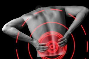 black and white image of a man grabbing his lower back in pain with a red target on the pain point