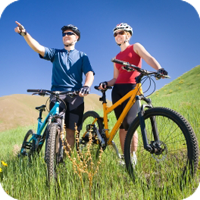 A man and woman riding their bikes on a grassy trail