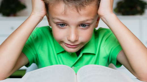 Image of a boy looking confused while reading a book.