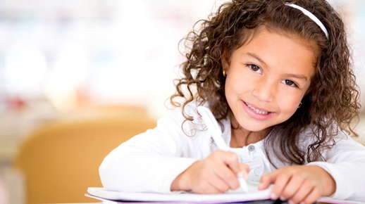Image of a little girl smiling and writing.