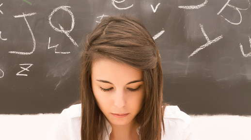 Image of a teenage girl looking down with a chalkboard behind her.