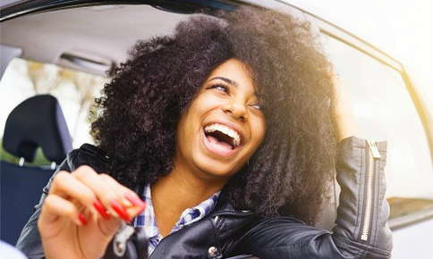 Woman with white teeth leans out of car window