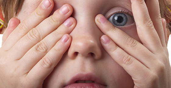 Image of a child peering out from between their fingers.