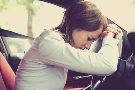 Image of a stressed out woman in her car.