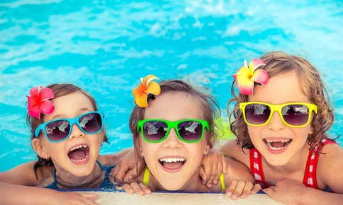 Happy kids in a pool wearing funky sunglasses