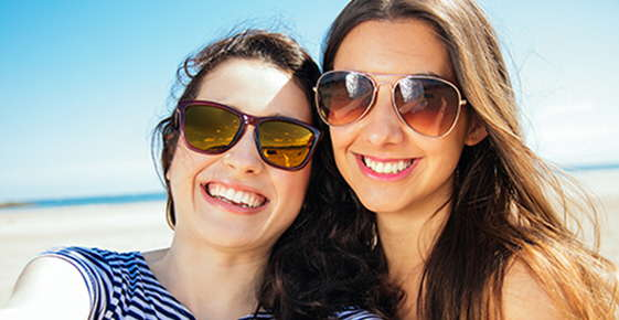 Image of two women wearing sunglasses.