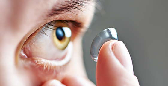 Image of someone putting in a contact lens.