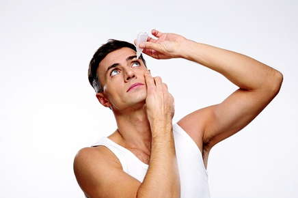 Image of guy using eye drops.