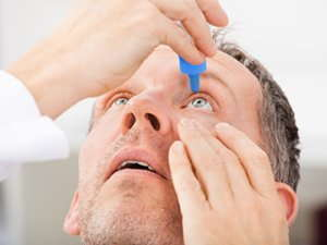 Image of a man using eyedrops.