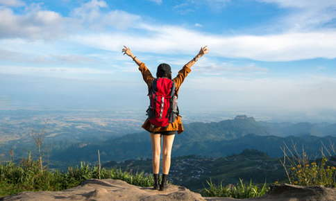 An image of a female backpacker who is standing on top of a mountain, in a victorious stance with both of her arms raised high.
