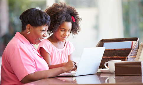 An image of a mother and young daughter smiling while looking at a laptop screen.
