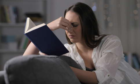Woman struggling to read book