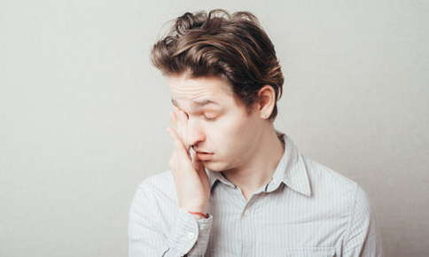 Image of a man rubbing his itchy eyes.
