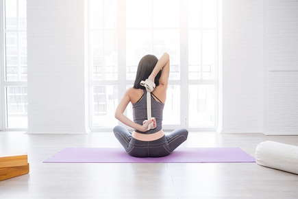 Image of a woman doing yoga with a stap.