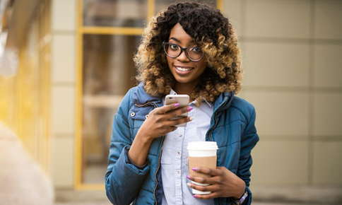 Image of women wearing glasses who is outdoors with her cellphone in one hand while holding coffee in the other.