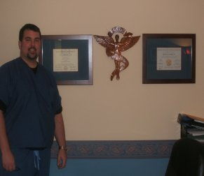 Dr. Conrad standing in front of plaques on a wall - North Wales PA Chiropractic office