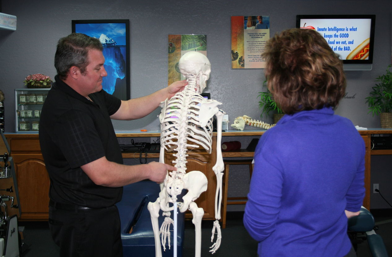 Doctor showing a patient the spine and how it relates to health and wellness
