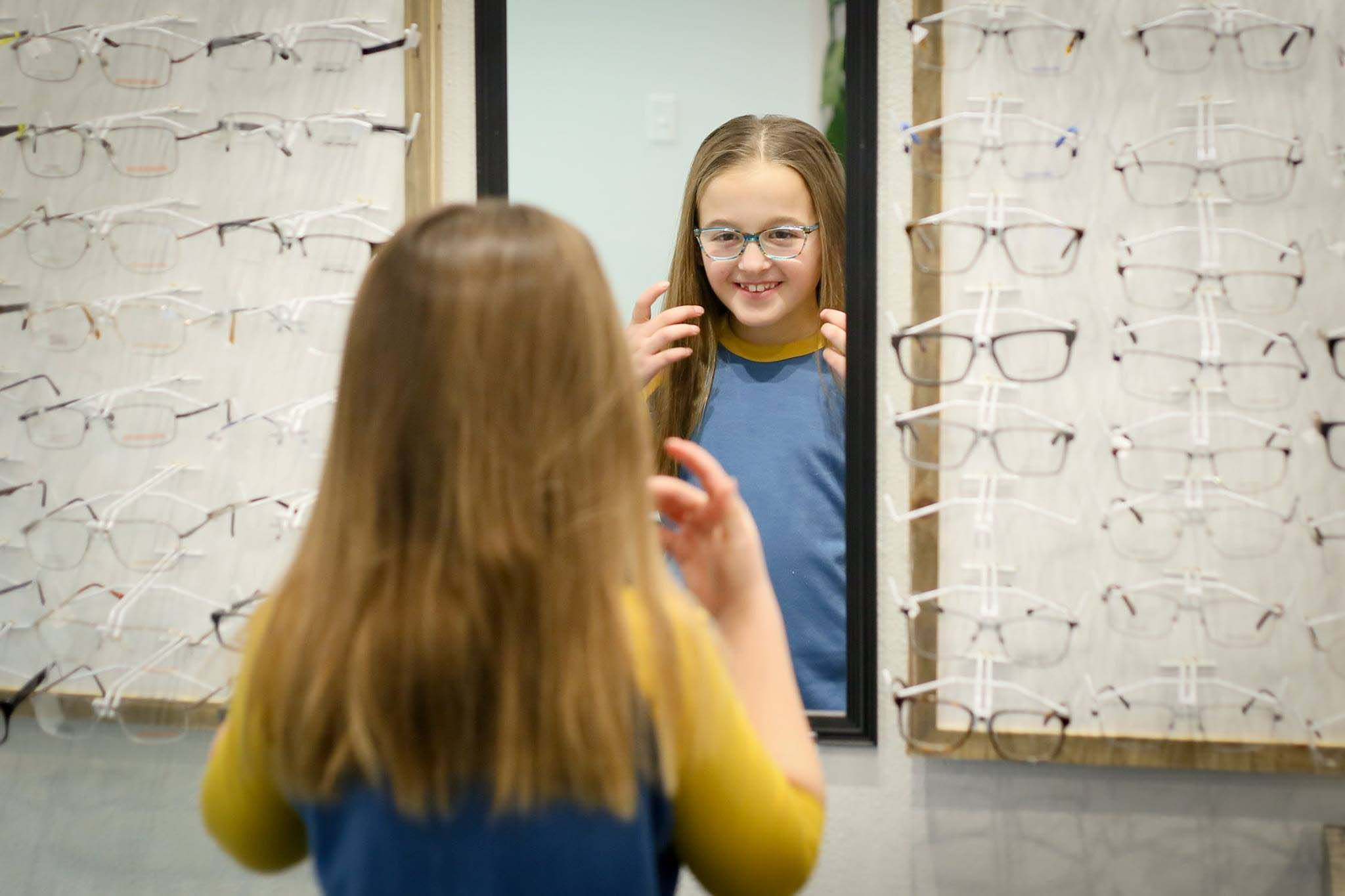 young girl trying on frames