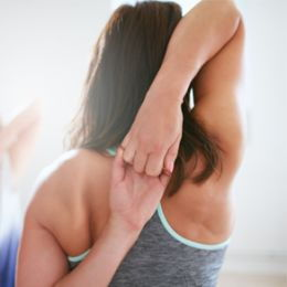 A woman locks her arms behind her back to stretch