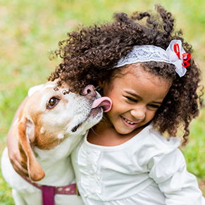 dog licking little girl on the chin