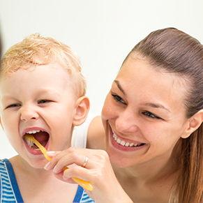 Mother brushing teeth of her toddler son